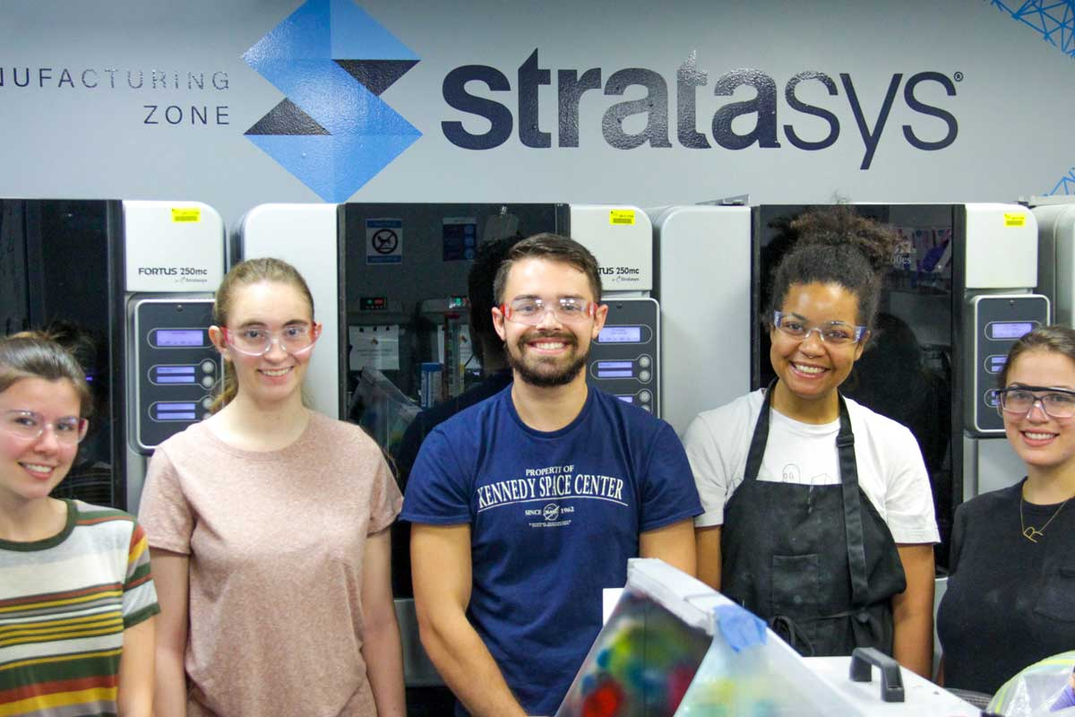 Five people stand in lab under the sign Stratasys sign