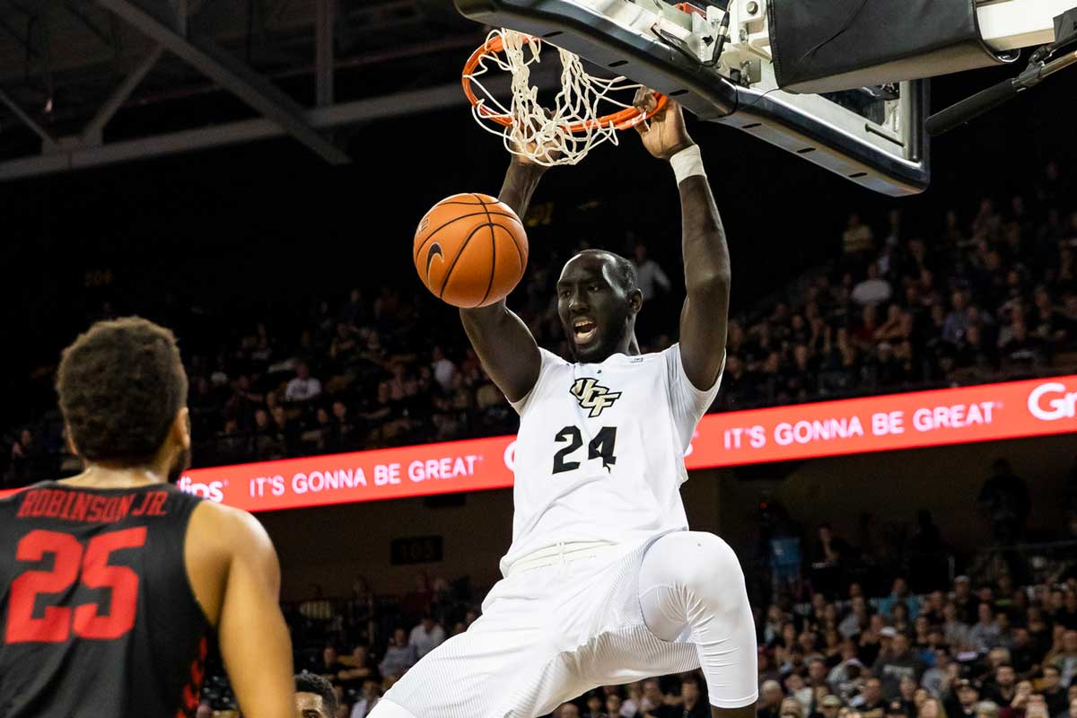UCF basketball player Tacko Fall dunks while opponent looks on