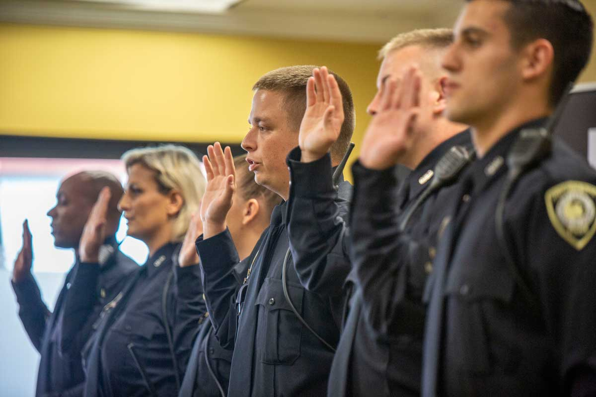 Six officers stand shoulder to shoulder with right hand raised to take oath