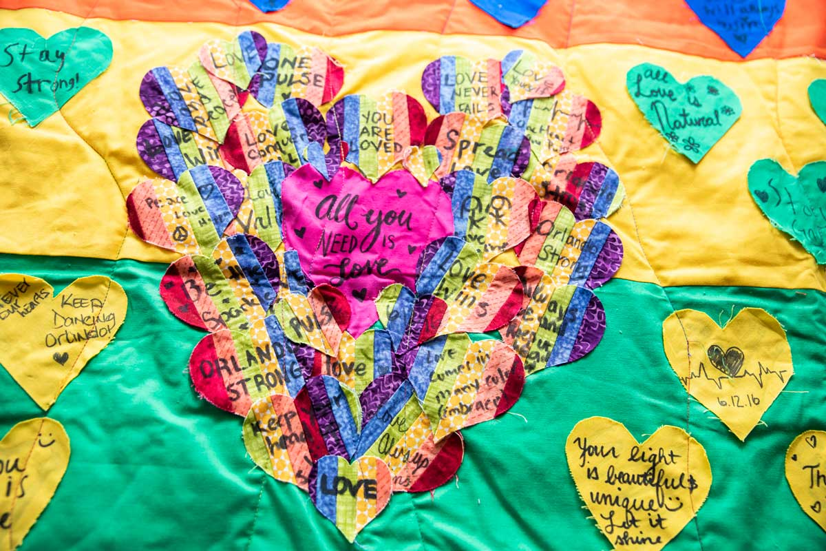 multi color quilt with a heart stitched in the center