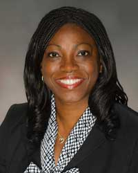 African-American woman in black blazer and black and white shirt