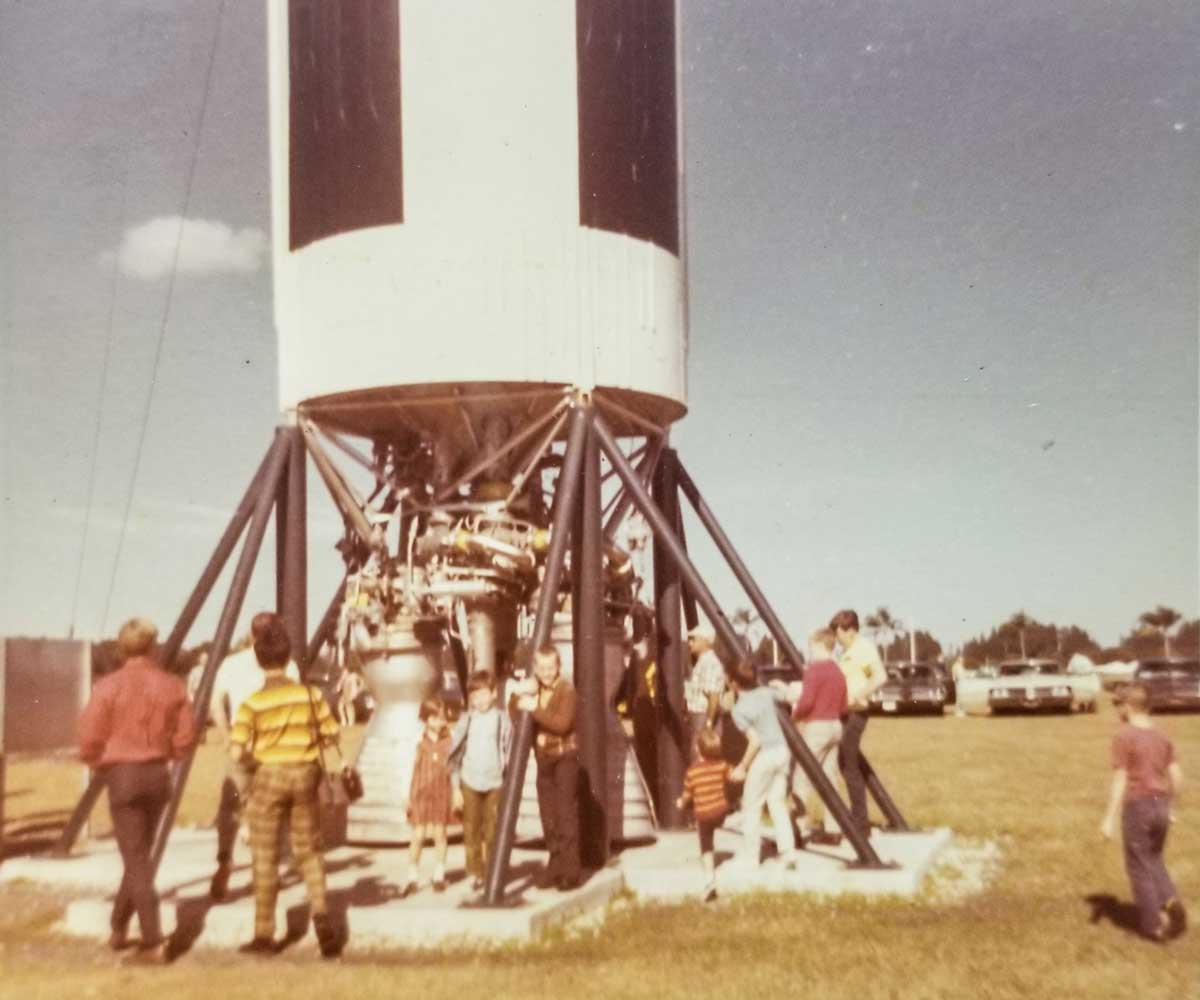 old photograph of the bottom of Apollo 11 and people walking around it on a sunny day