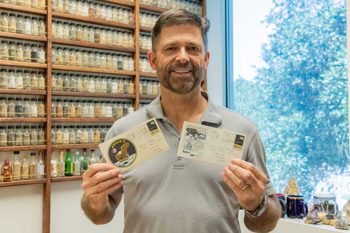 Man with beard wearing gray polo shirt stands in front of dirt samples and holds two post cards in hand