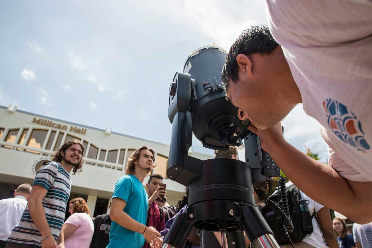 Student looks into telescope in front of Millican Hall