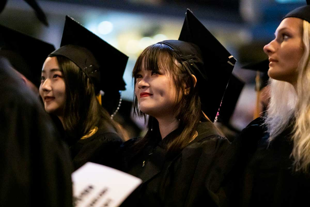 Three females in cap and gowns stand at graduation ceremony