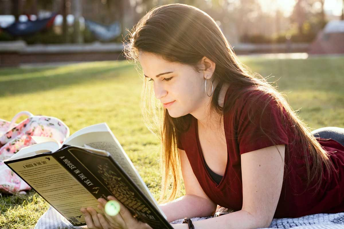 Young woman lays on stomach reading a book outside on the grass