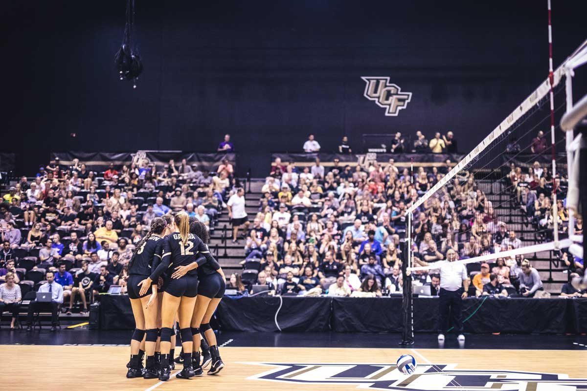 volleyball team huddles on court in front of crowd