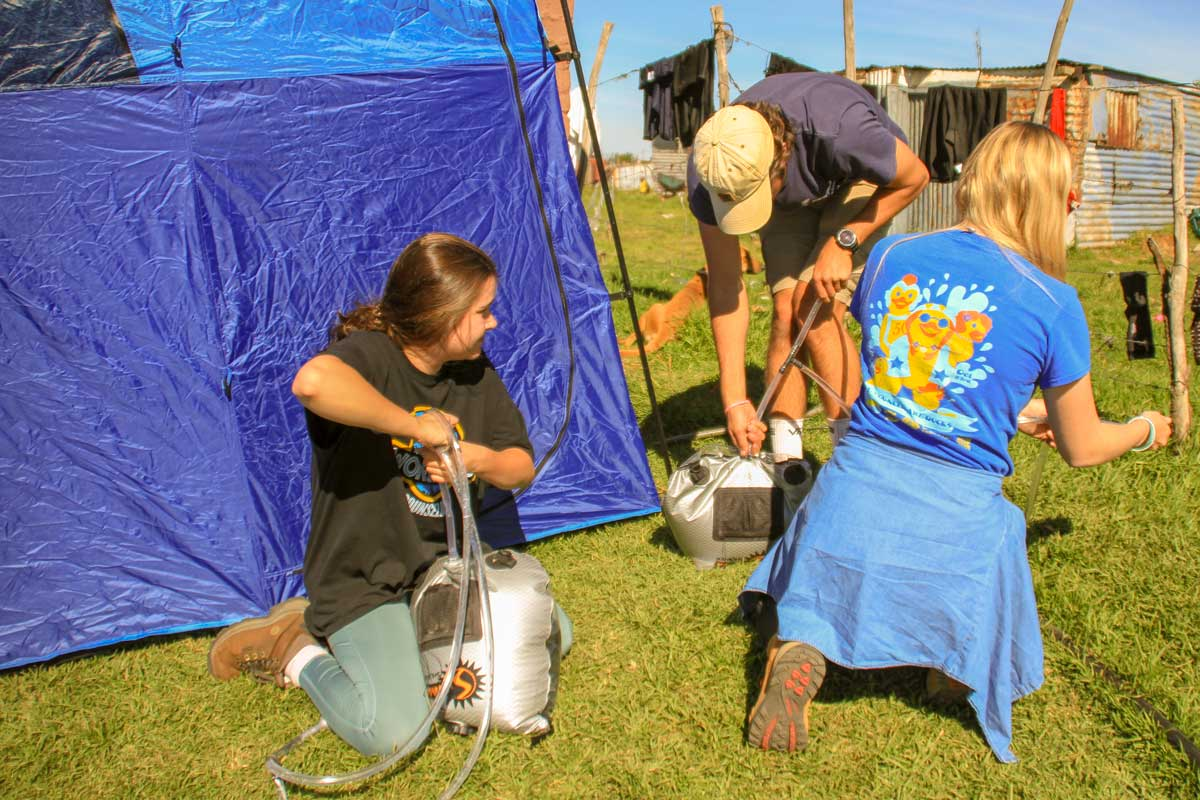 Three UCF students kneel next to blue tent to construct makeshift shower