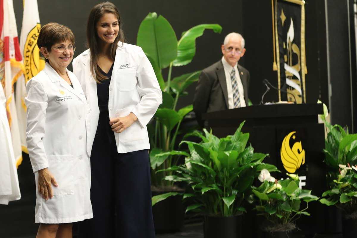 Lisvet Luceno stands on stage next to College of Medicine Dean Deborah German