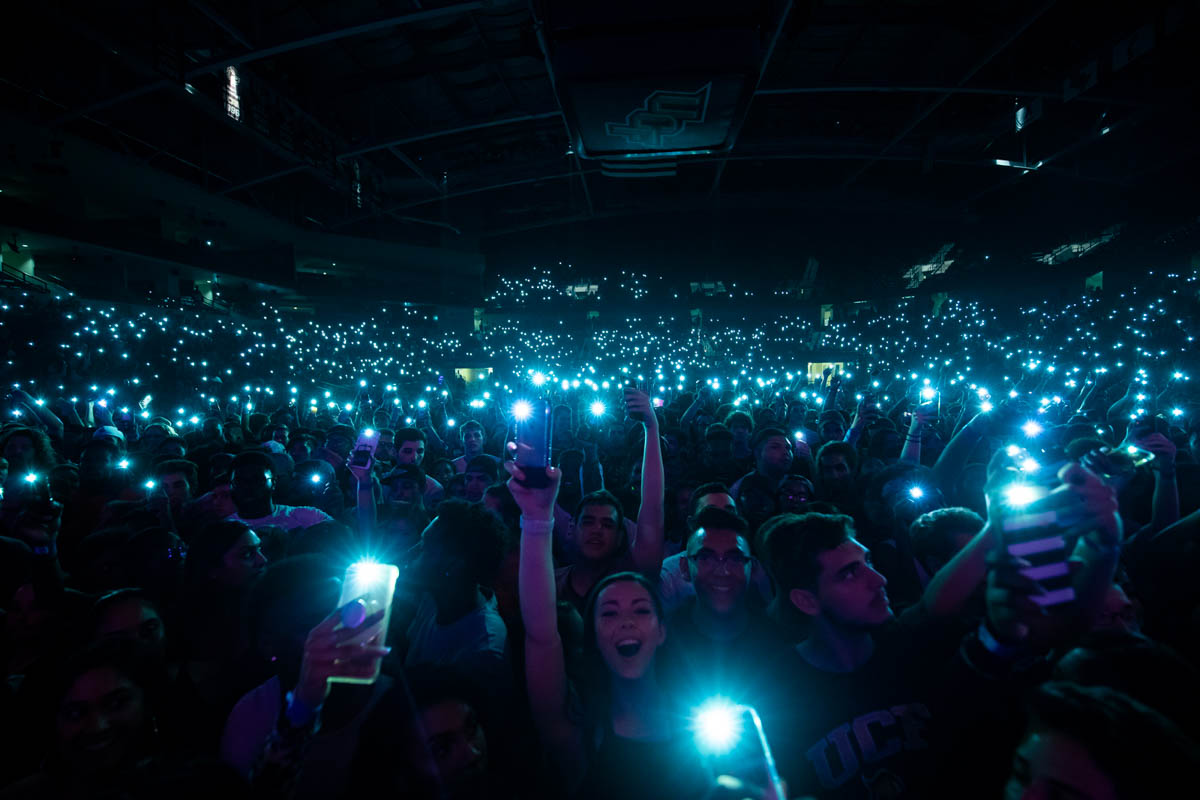 Dark arena with crowd holding up cell phone flashlights