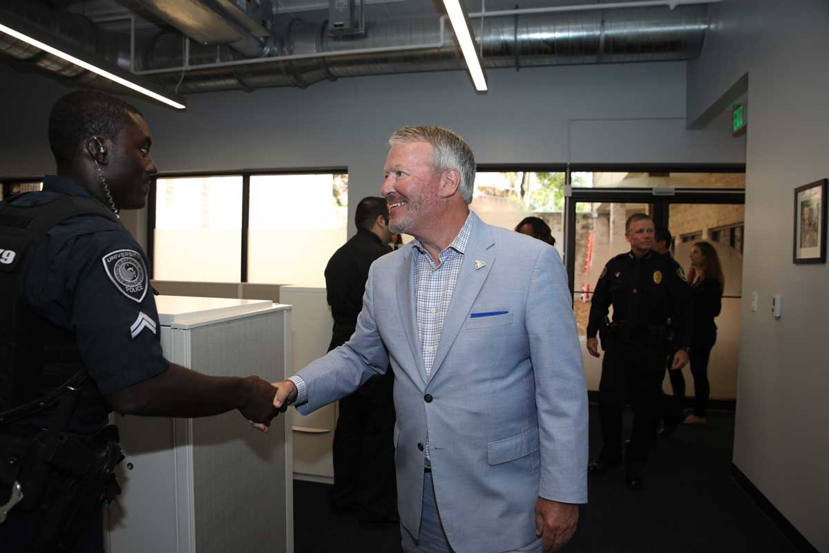 City of Orlando Mayor Buddy Dyer shakes hands with police officer in downtown station