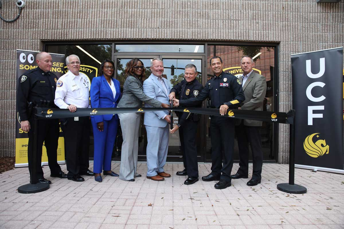 Eight people stand shoulder to shoulder to help cut a ribbon in front of UCF Police's new station at downtown