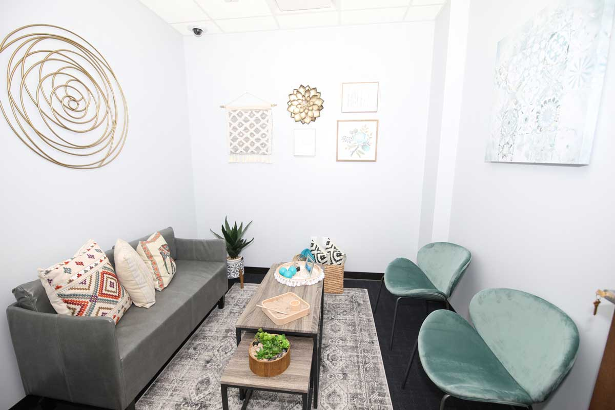 Soft interview room with a gray couch and pillows, coffee table and two green chairs