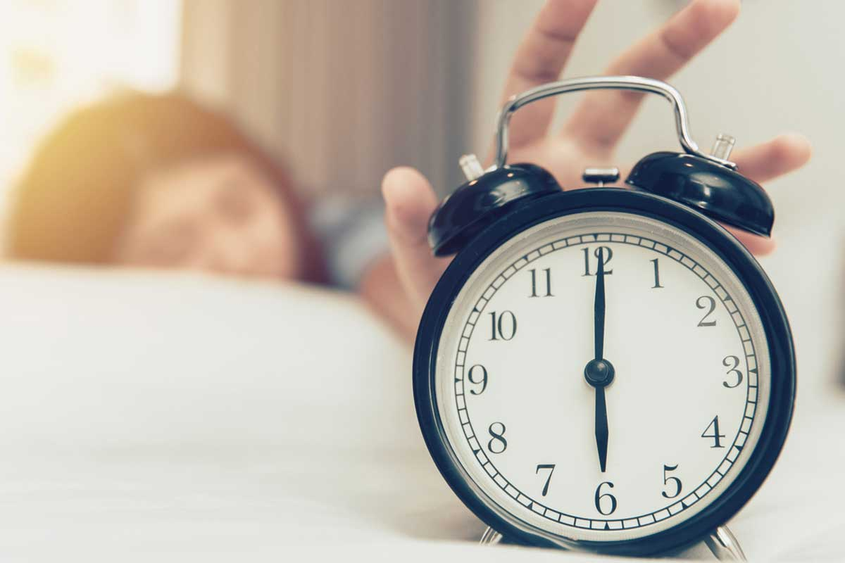 Woman reaches for alarm clock reading 6 a.m.