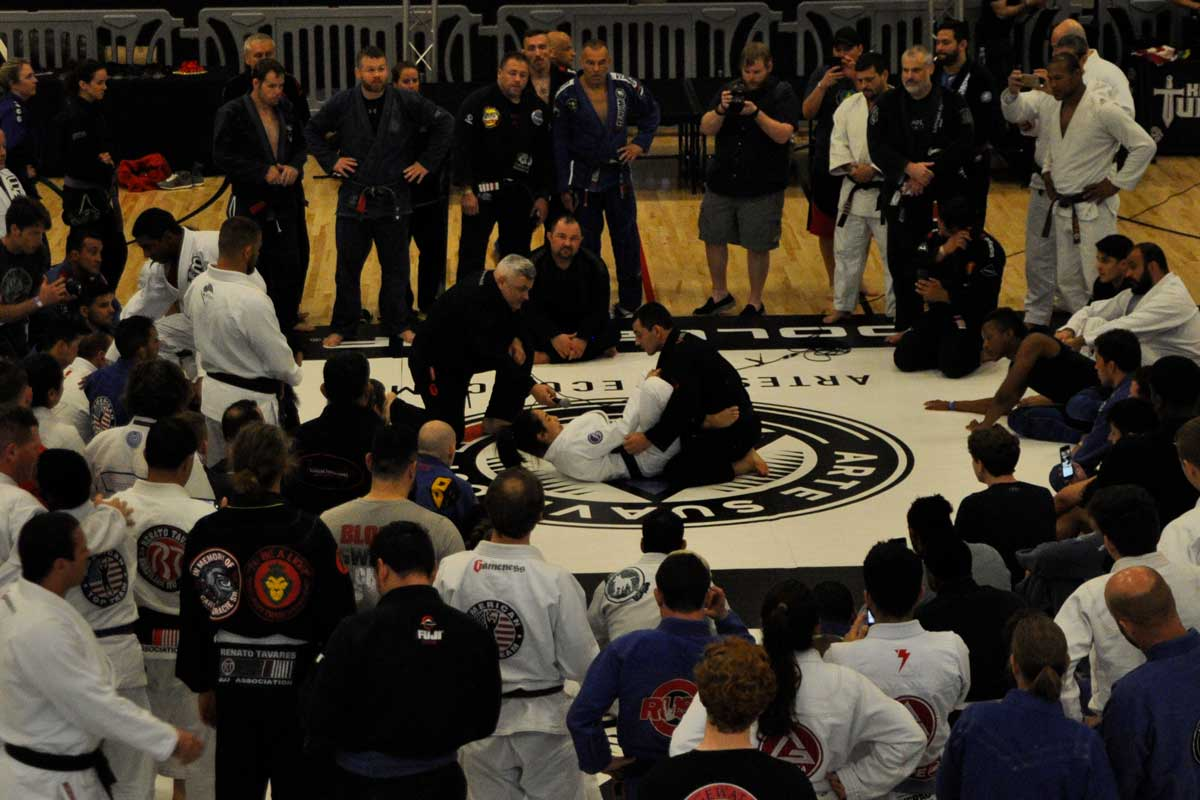 Two men in middle of mat surrounded by circle of onlookers engage in Brazilian Jiu-jitsu