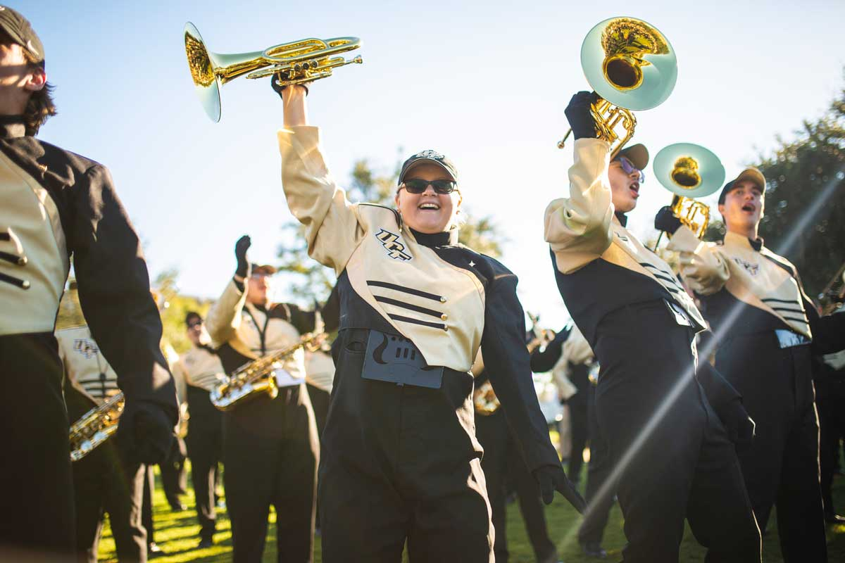 Members of UCF's marching band in black and gold uniforms hold up horns