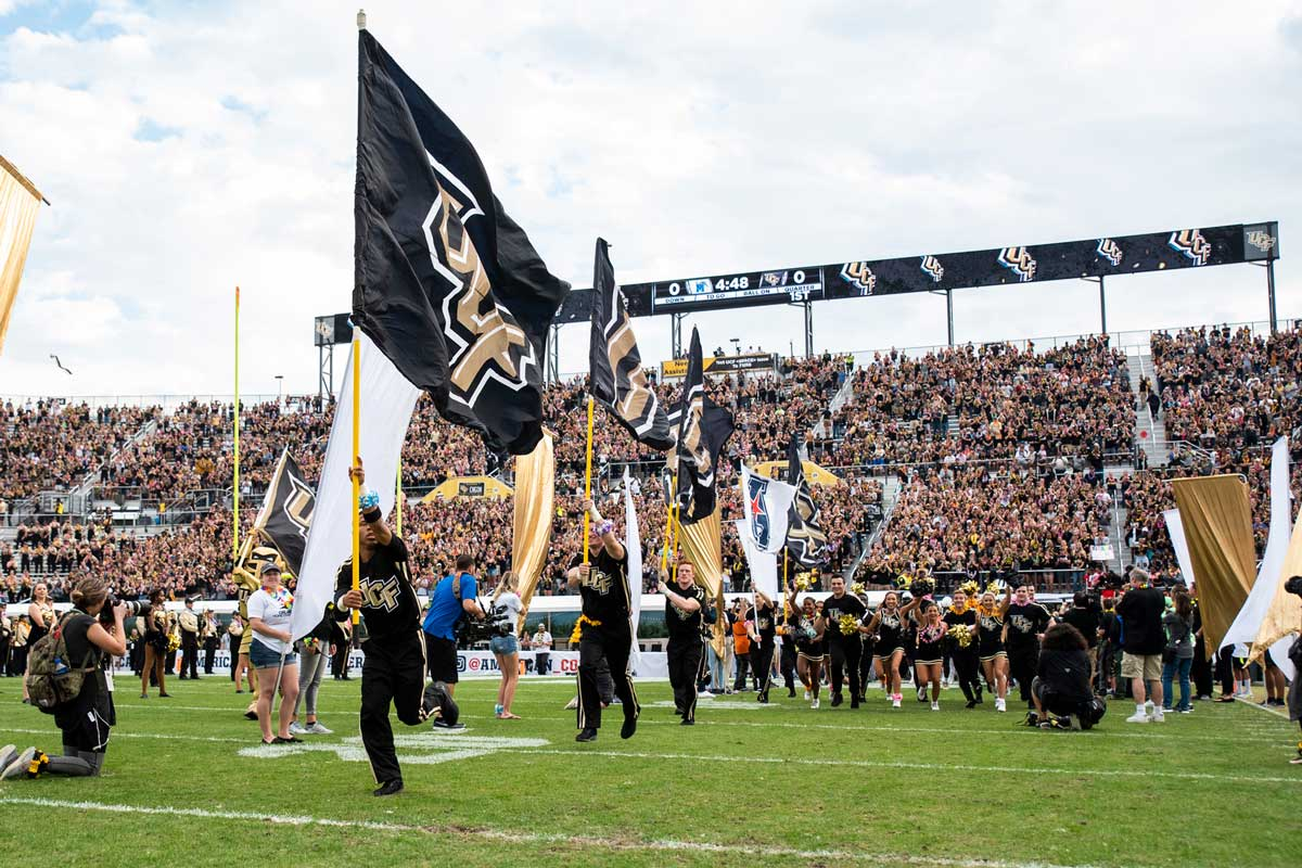 Cheerleaders holding UCF flags storm out onto football field
