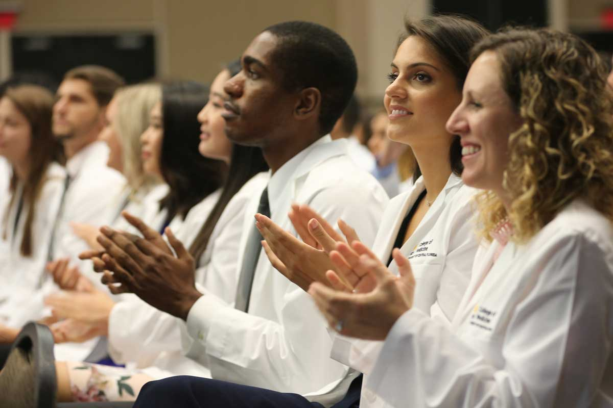 A row of medical students sit and clap