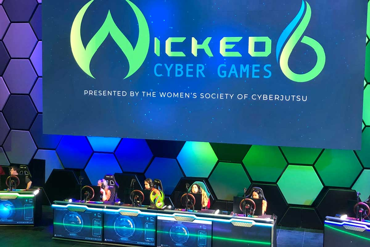 Four women sit at a table on blue green stage with headsets on