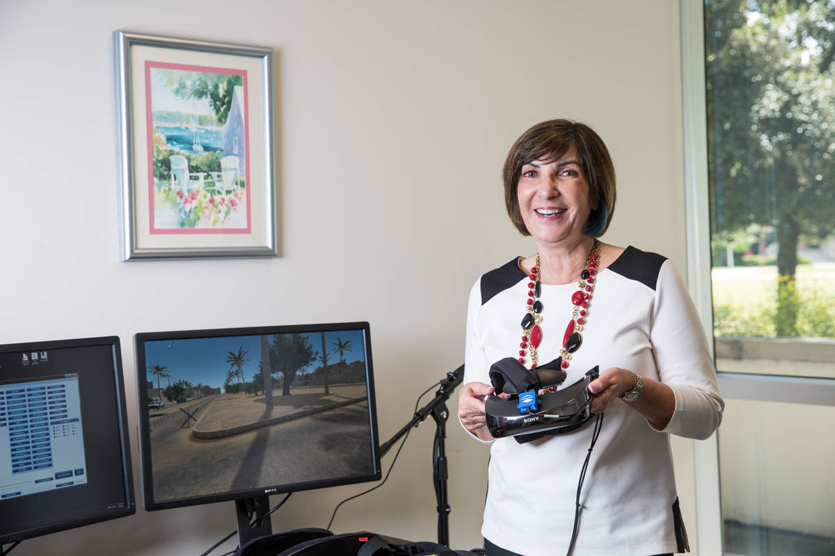 A woman holds a virtual-reality headset while smiling.