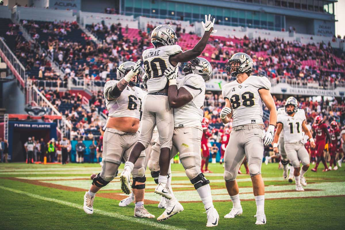 UCF football player Greg McCrae lifted into the air in celebration by his teammates in the end zone