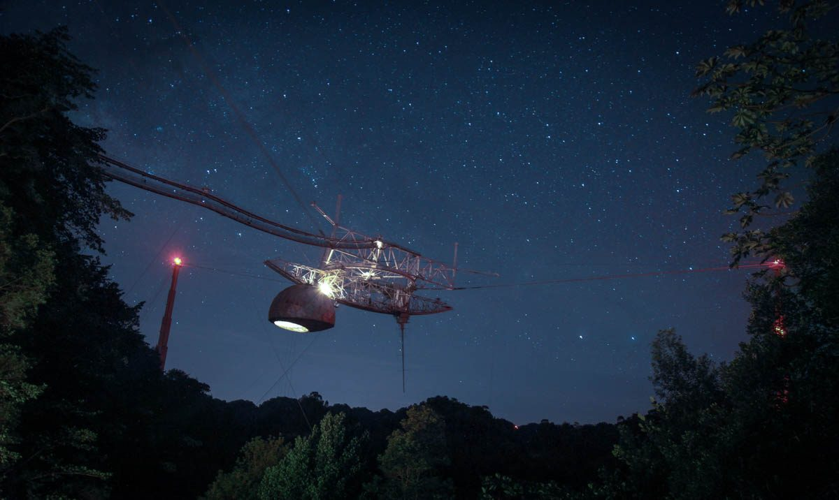 The Arecibo Observatory hangs in a star-lit sky