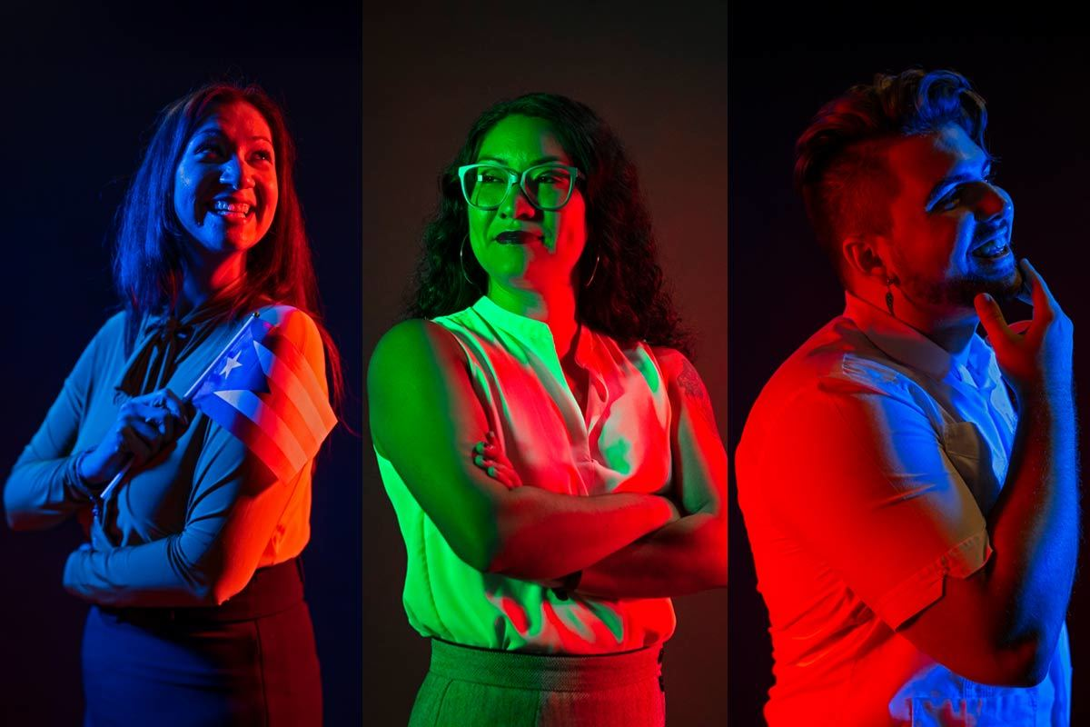 Three people pose with pride under colored lights.