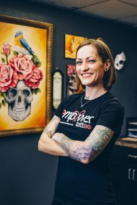 Nipple tattoo artist Stacie Becker stands with her arms folded in her studio Empower Tattoo