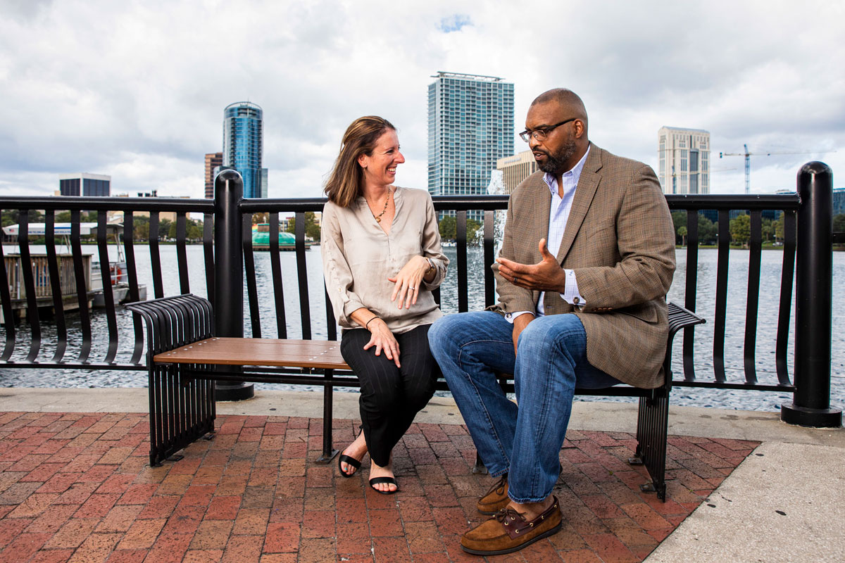 A white woman and a black man who are helping young stroke survivors sit on a bench and talk near Lake Eola