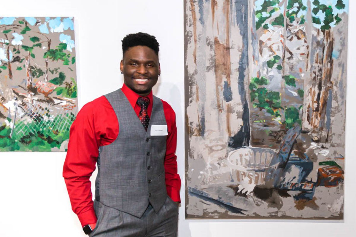 Titus Thomas next to a painting that shows the type of rundown house he used to live in as a young boy.