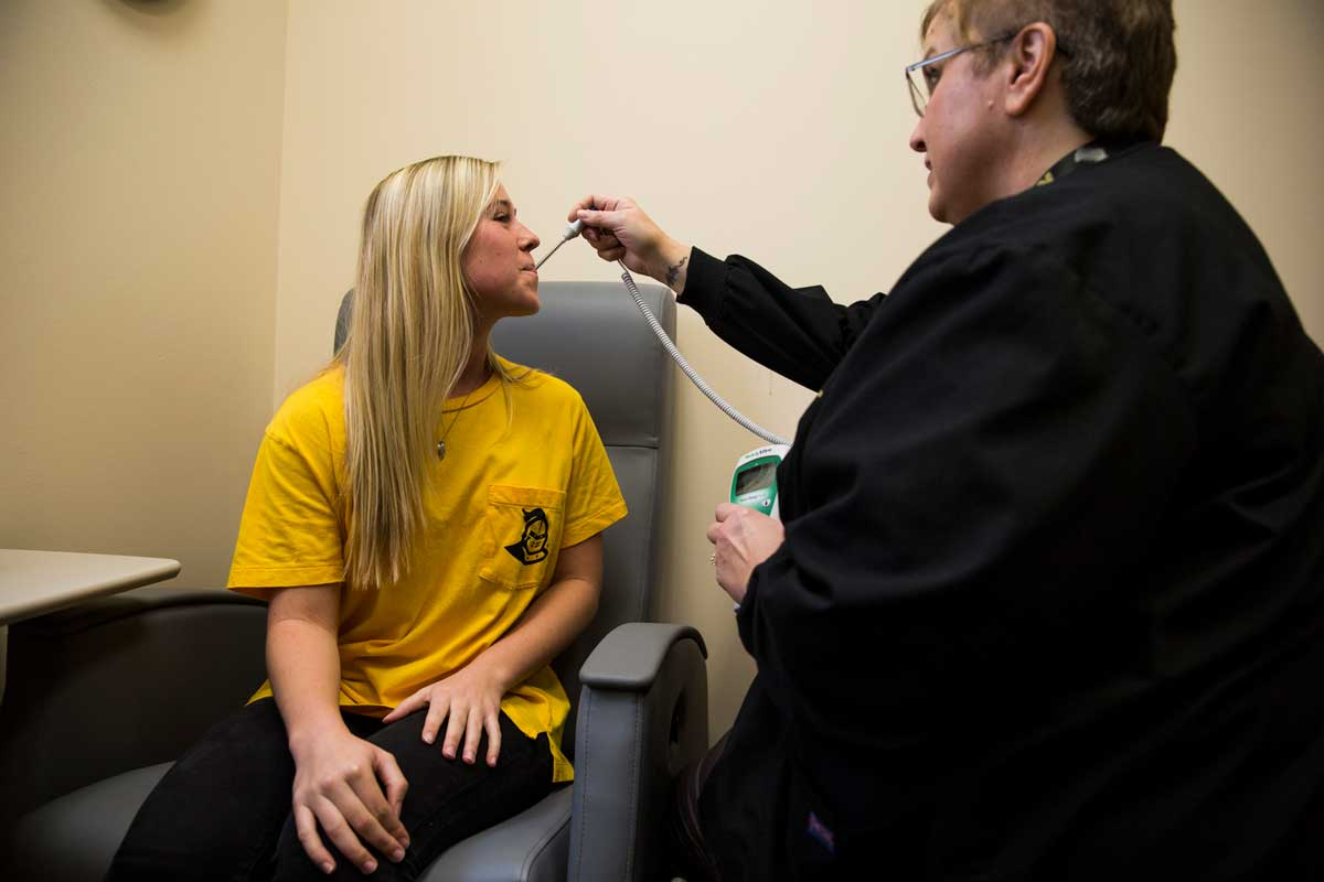 blonde woman gets temperature taken in doctor's office