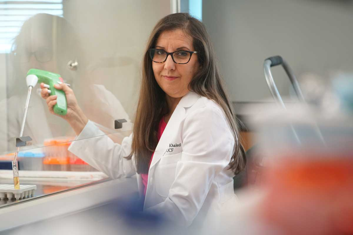 Annette Khaled wearing a white coat in a lab