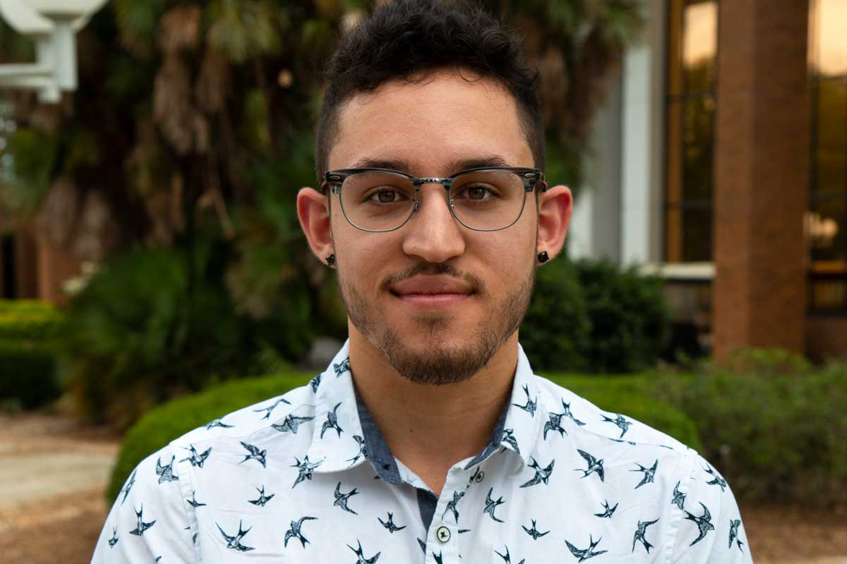 College-age male student wearing glasses and blue patterned collared shirt