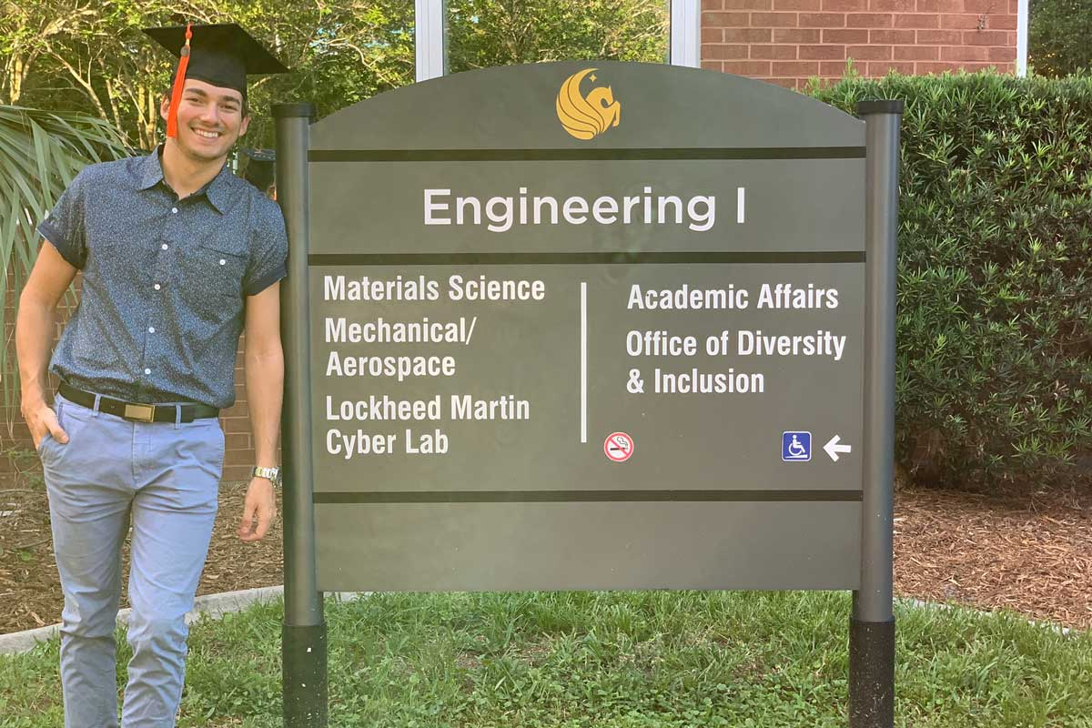 Juan Vila wears graduation cap while standing next to Engineering College sign