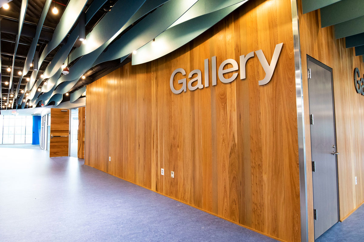 wood paneling wall with Gallery written in metal letters