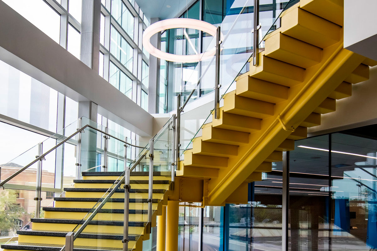 Yellow stairs with glass floor to ceiling windows surrounding them