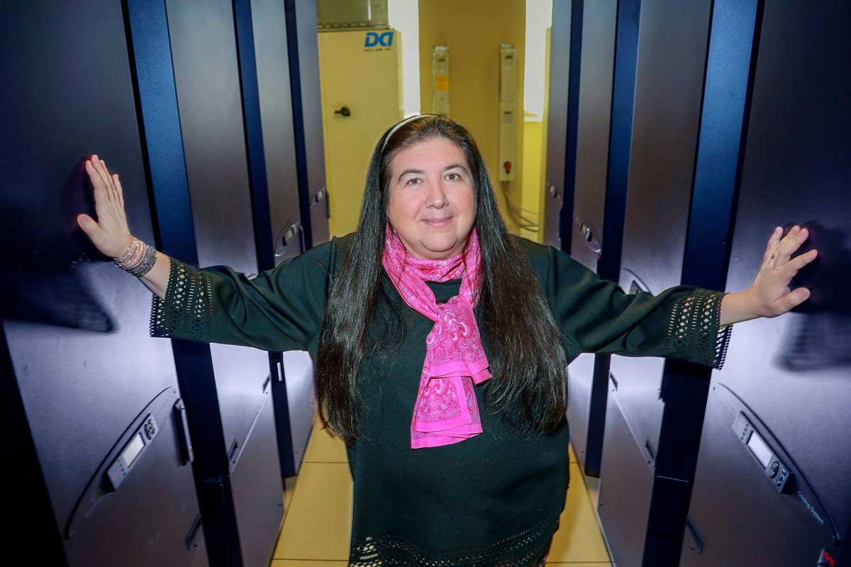 Woman wearing black long sleeve top and pink scarf stands in hallway with arms outstretched