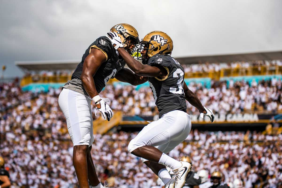 two football players with gold helmets, black jerseys and white pants, embrace in midair with stadium stands in background