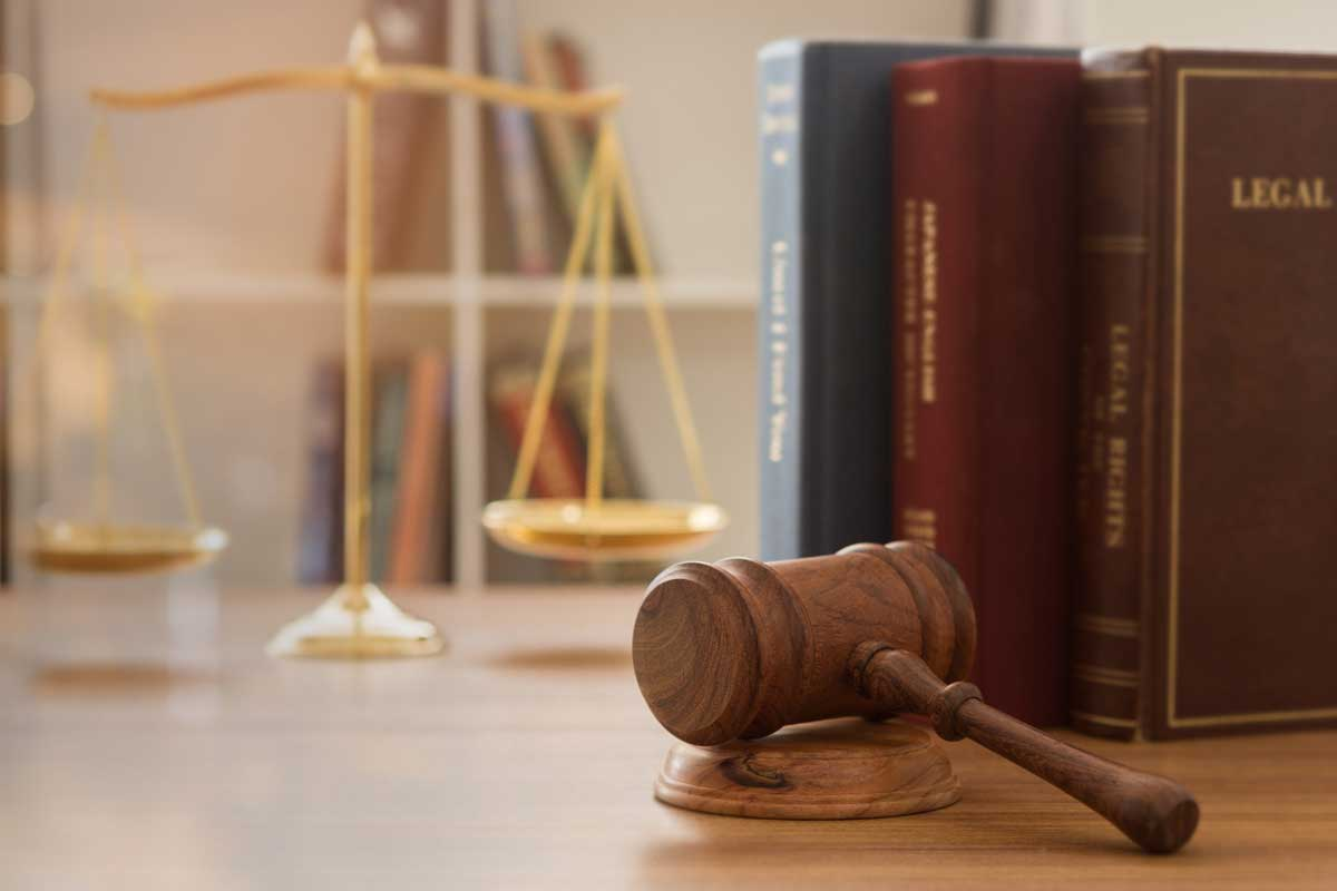wooden gavel placed on a desk near legal books and a gold scale in the background