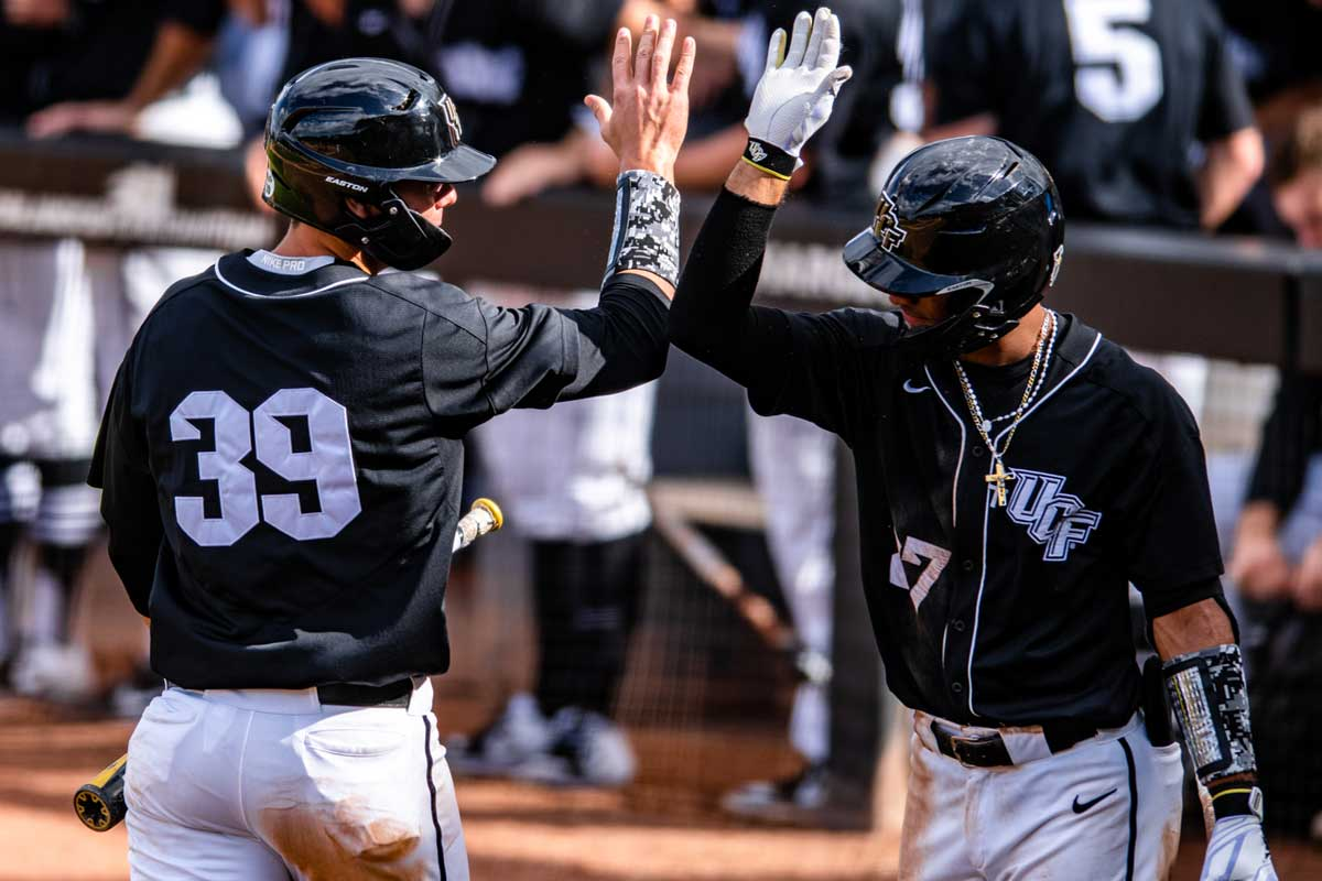 Two UCF baseball players give each other high fives near dugout