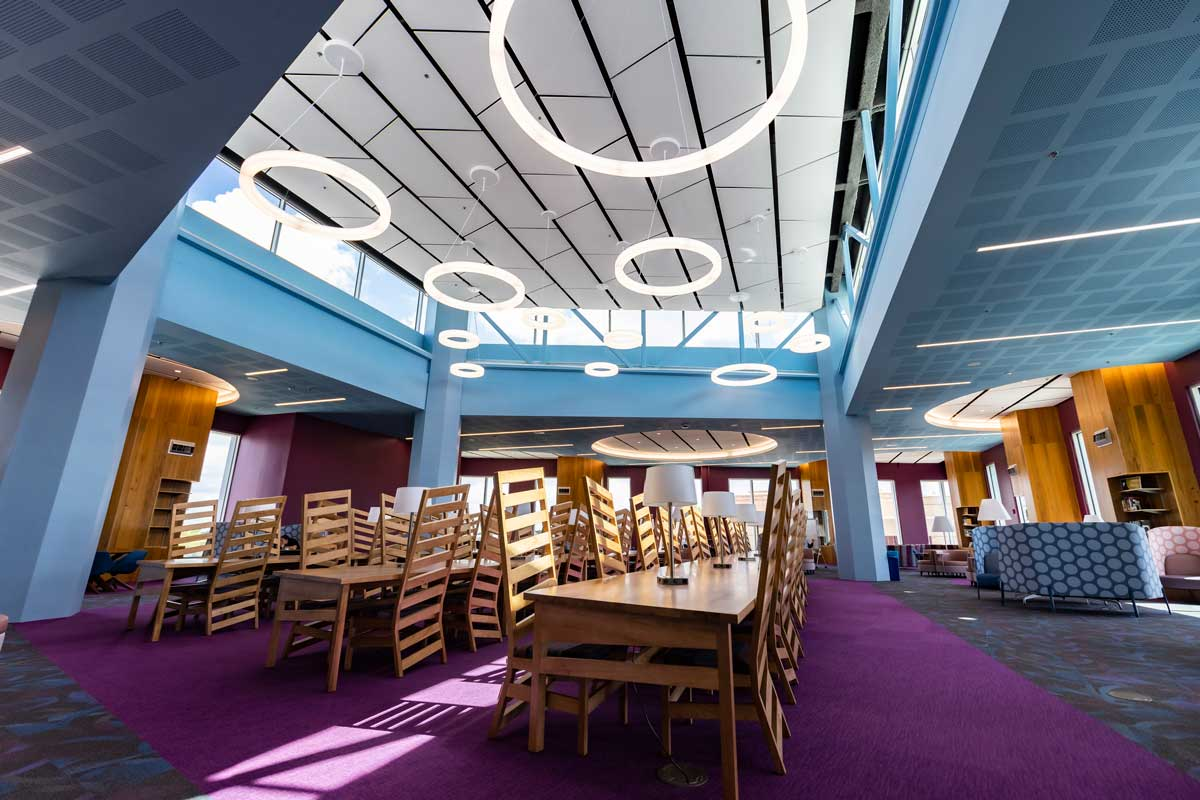 4th floor of Library featuring purple carpet, long wooden tables and chairs and circle lights