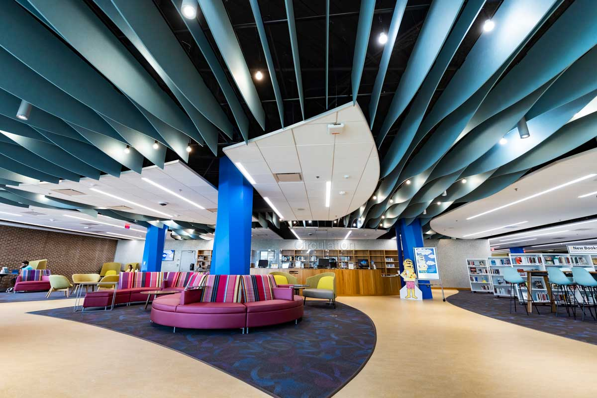 purple circular couches around blue poles in front of the circulation desk with white bookshelves off to the right