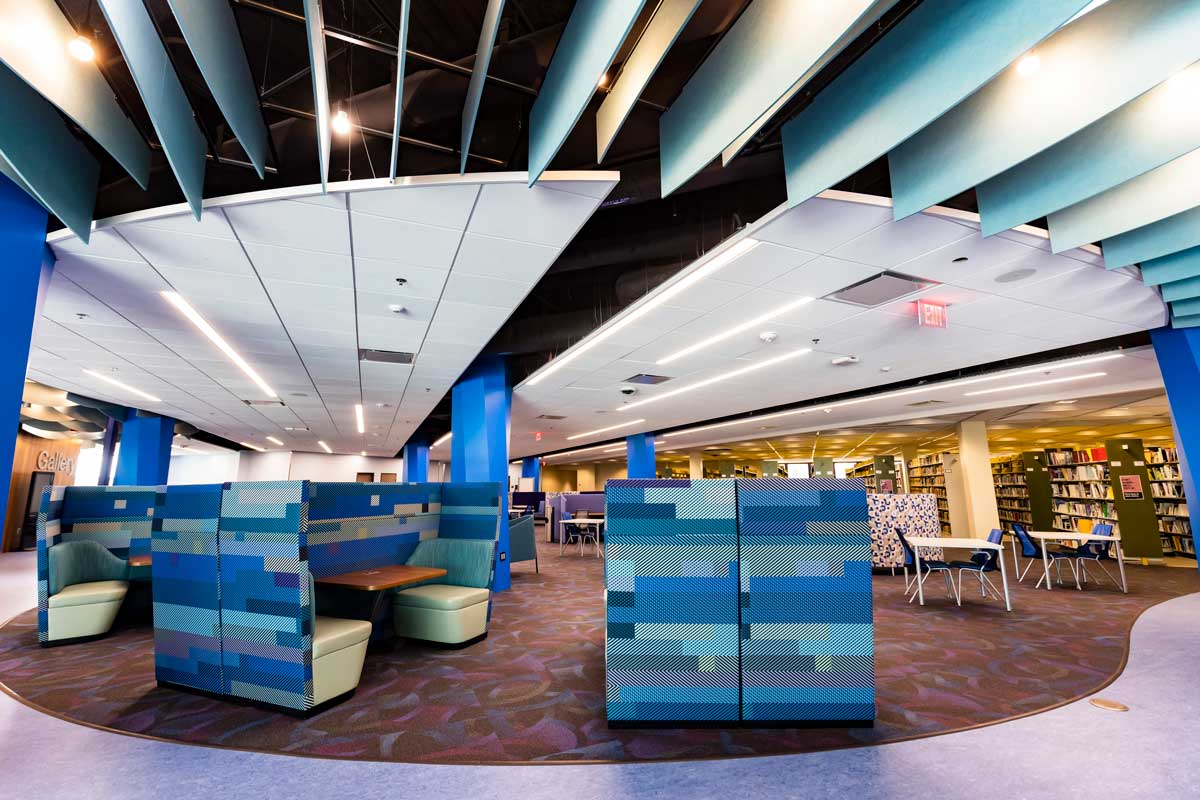 Blue high back chairs and tables on open floor with stacked bookshelves to the right