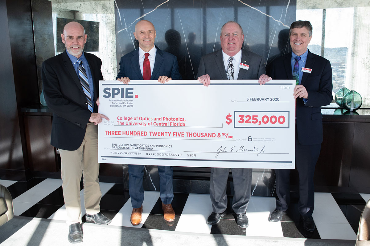 Four men in suits hold up a giant check in the amount of $325,000.