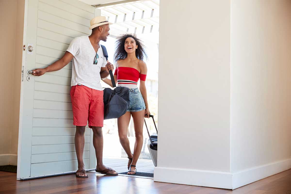couple arrives in vacation rental with luggage