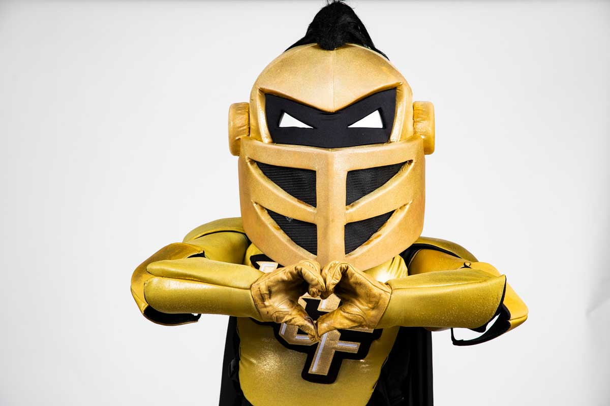 UCF mascot Knightro forms heart with his hands