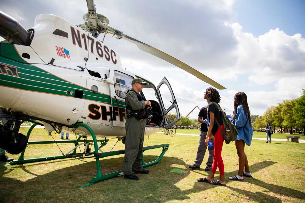 A police officer talks to two college students in front of a Sheriff helicopter parked on Memory Mall