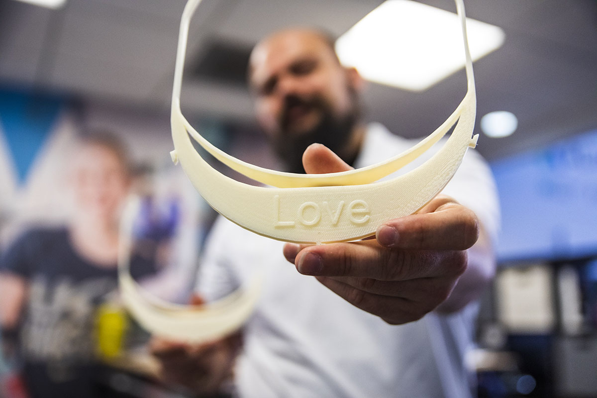 "closeup of white 3D-printed visor with message ""Love"" etched in bill"