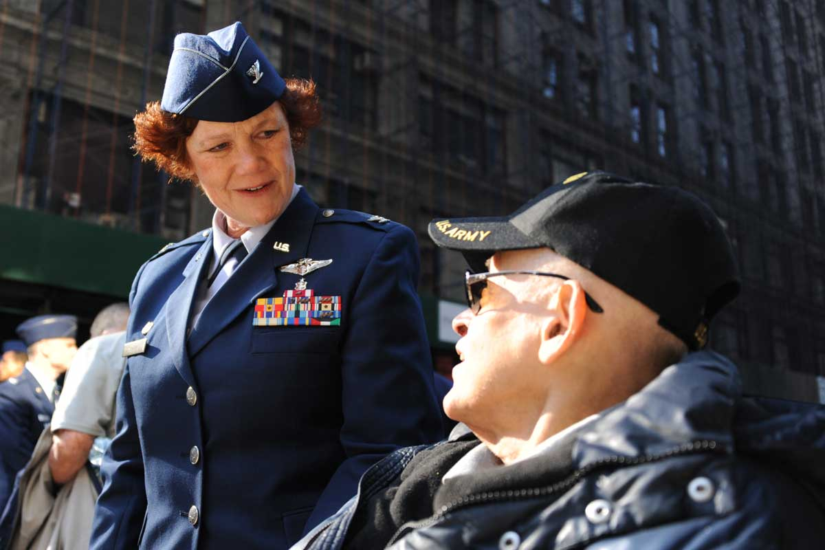 Woman in blue uniform speaks to seated man wearing veteran ballcap