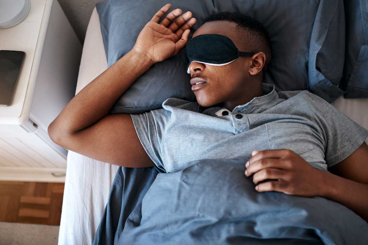male wearing black eye mask sleeps with his arm relaxed on pillow in bed